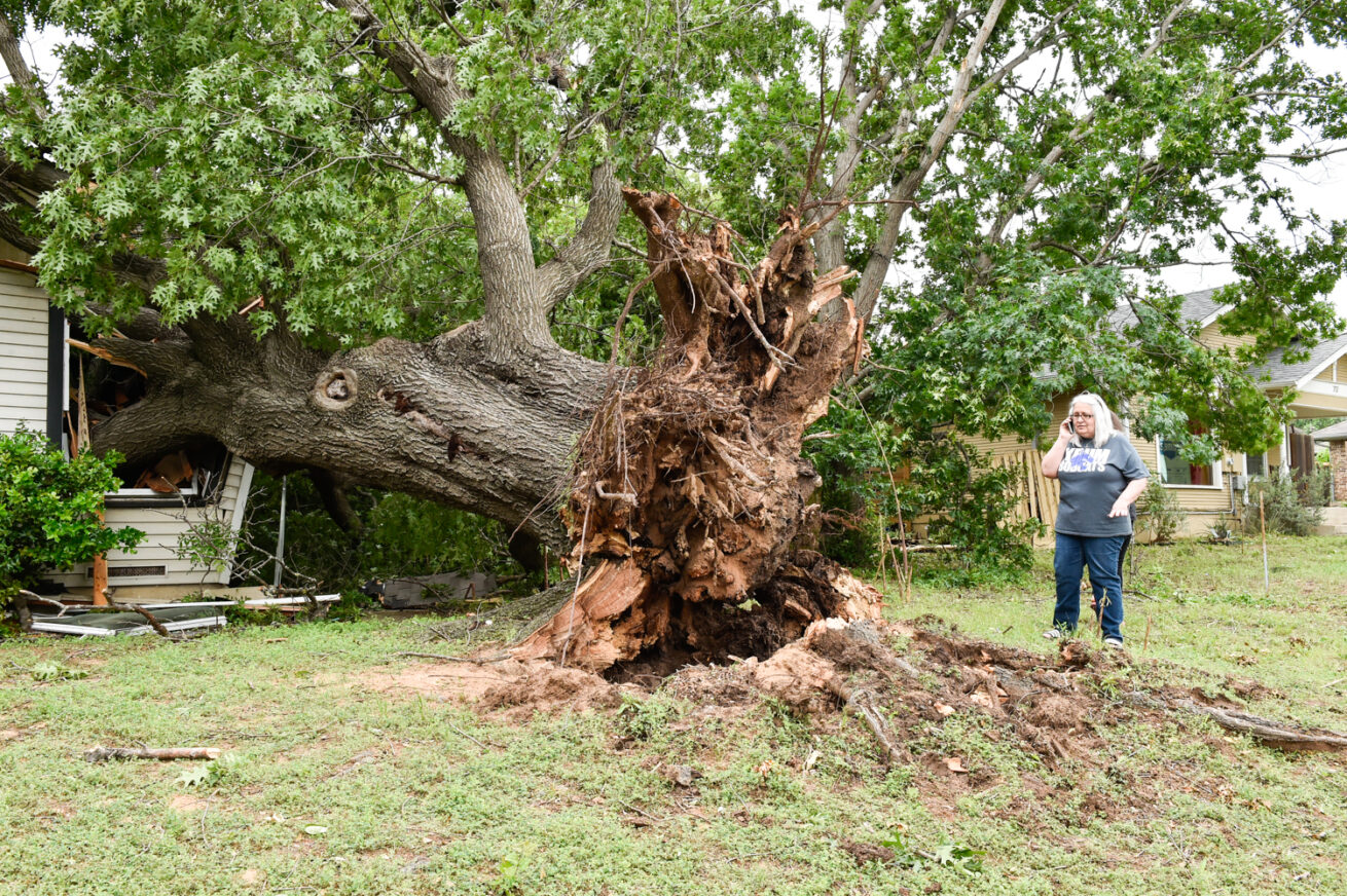 Resident Jacqueline Jackson looks over the damage caused by a tree that fell on her residence near the 700 block of Roberts Street, Wednesday, May 1, 2019, in Denton, Texas.  A tornado briefly touched down Tuesday evening northeast of the Texas Woman's University campus, National Weather Service officials confirmed.