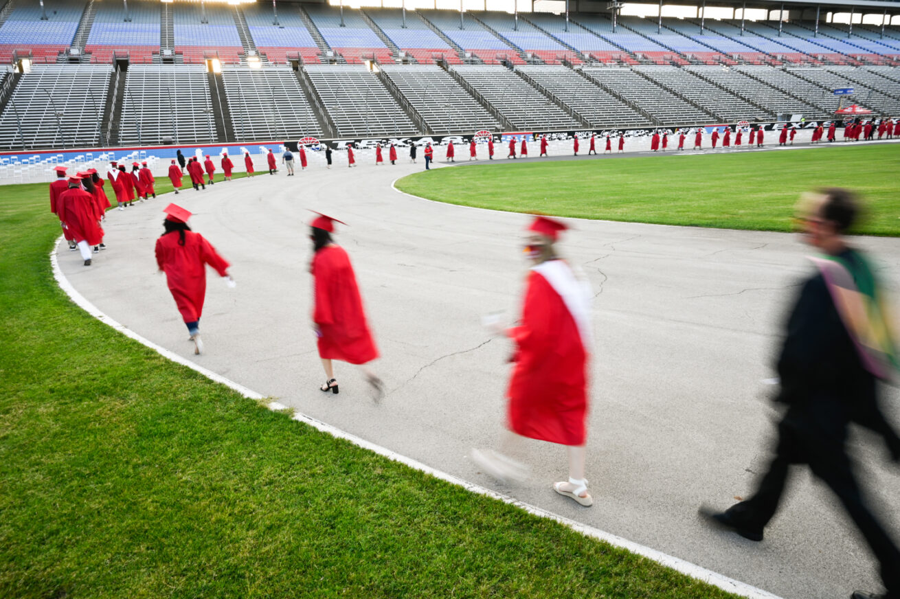 Students walk to their seats before they receive their diplomas during the Ryan High School graduation ceremony at the Texas Motor Speedway, Thursday, May 21, 2020, in Fort Worth, Texas..JPG