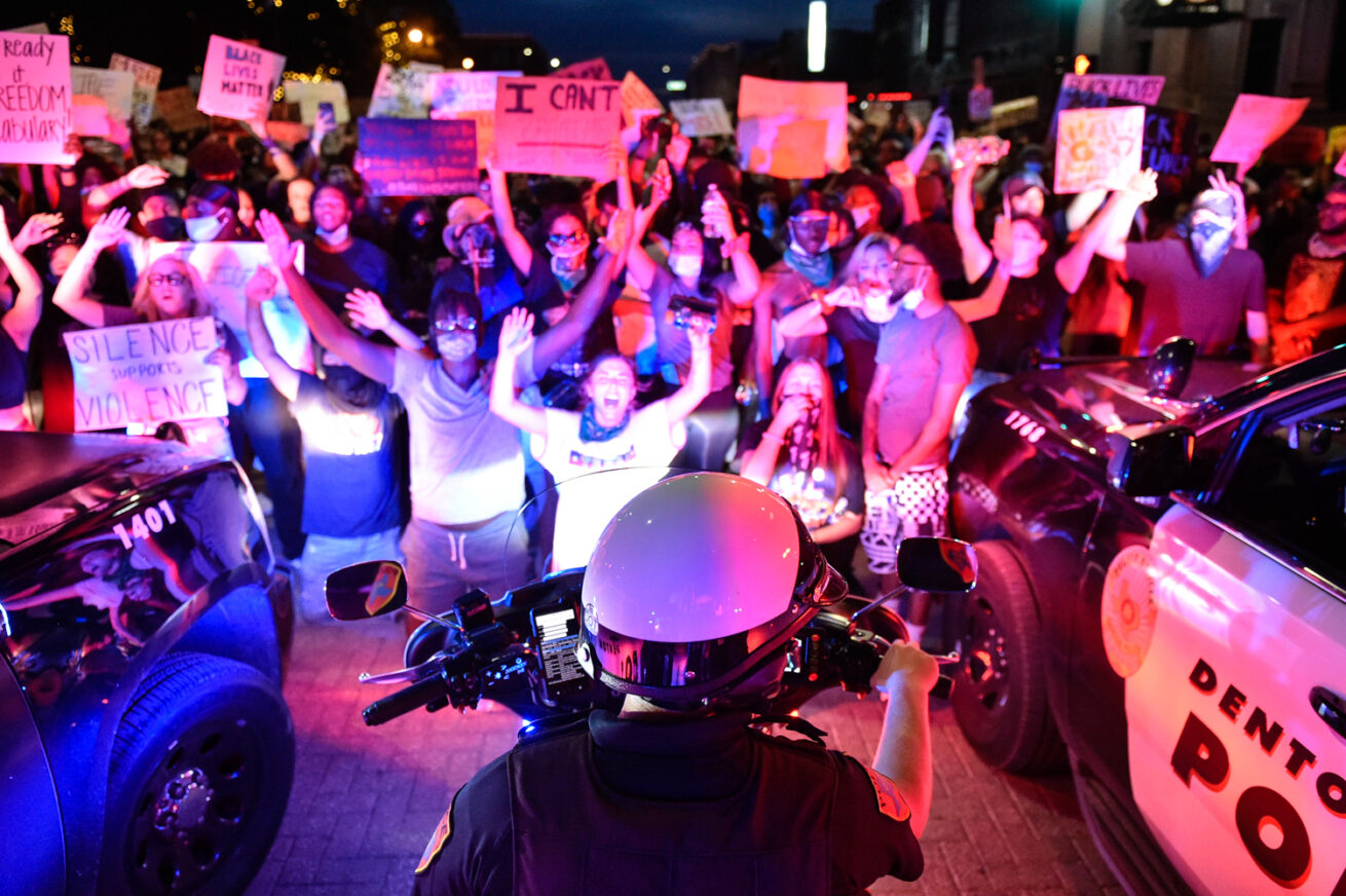 Denton police patrol downtown, while protesters chant at them, Monday, June 1, 2020, in Denton, Texas.  Two separate protests came together in downtown Denton Monday night to have thousands of people listen to stories of police violence and racial inequality..jpg