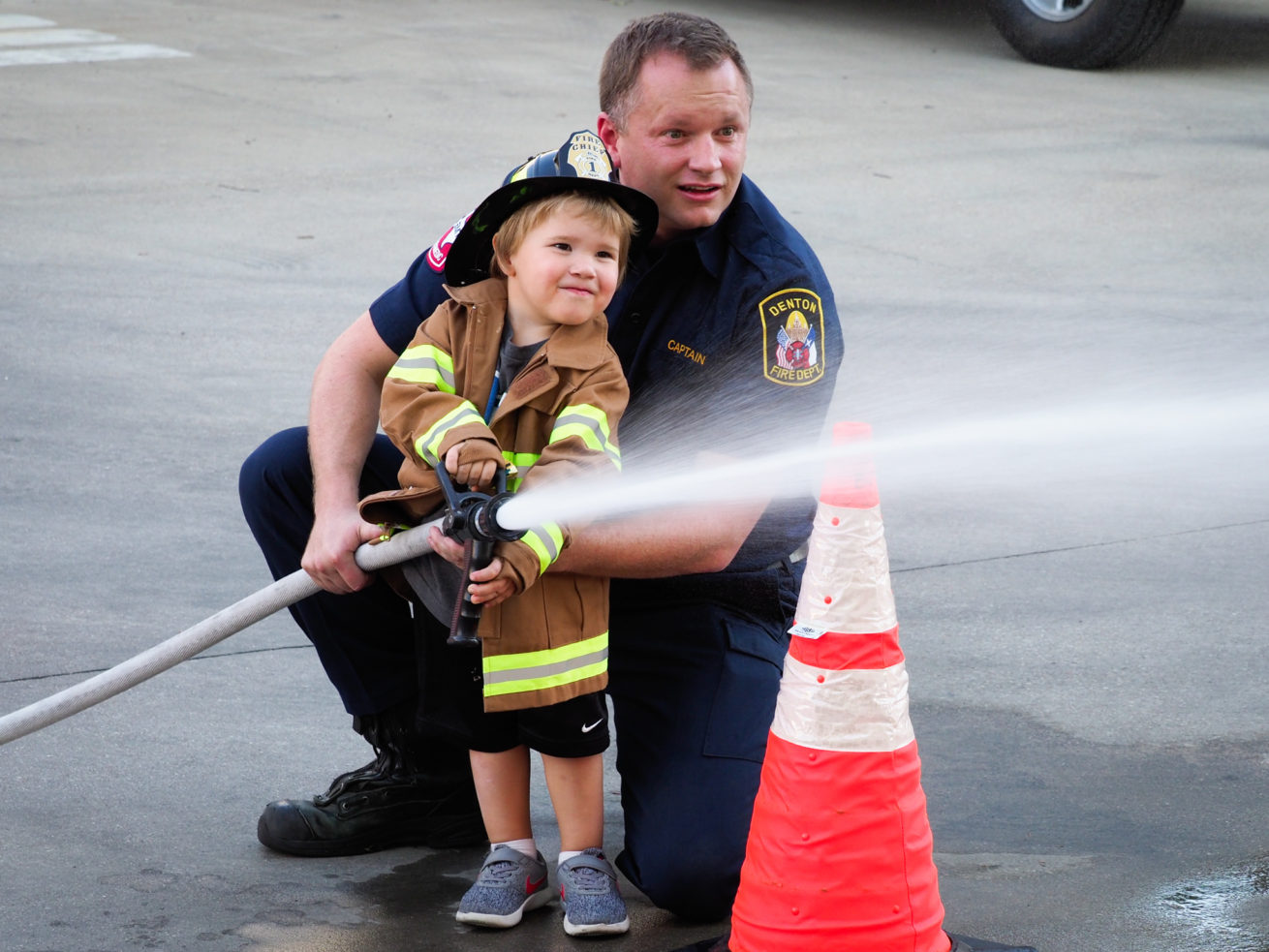 Denton fire training captain, Collin Skipper, teaches 3-year-old, Riley Platt, how to use a fire hose during the annual Public Safety Day event at Central Fire Station.  The Denton Fire Department and Denton Police Department hosted a dedication to the 9/