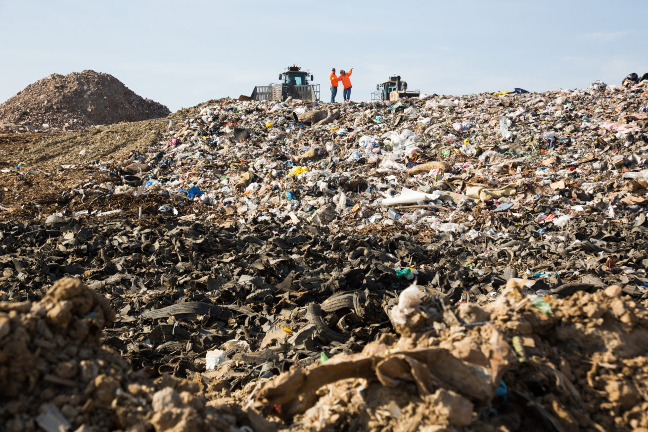 The two workers stand on top of a hill of garbage in landfill section at ECO-W.E.R.C.S. Resource Recovery Park