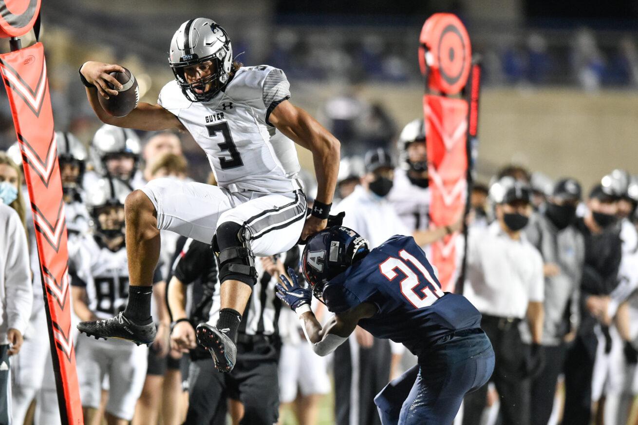 Guyer quarterback Eli Stowers (3) leaps over Allen's Nicholas Bargains (21) at Eagle Stadium, Friday, Nov. 13, 2020, in Allen, Texas.