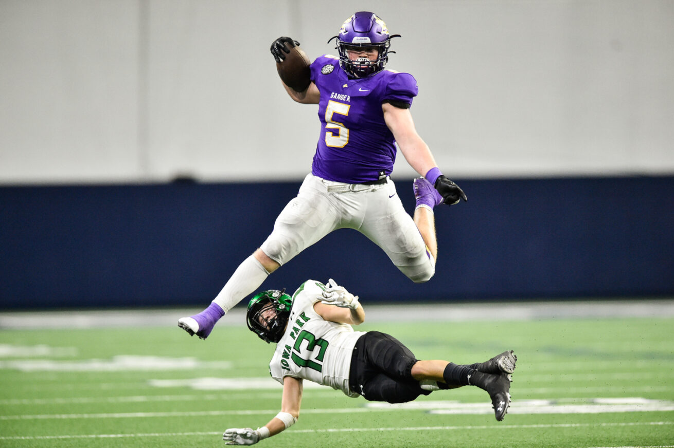 Sanger's Tallyn Welborn (5) leaps over Iowa Park's Korvin Lalumia (13) at the Ford Center at The Star, Saturday, Nov. 14, 2020, in Frisco, Texas.