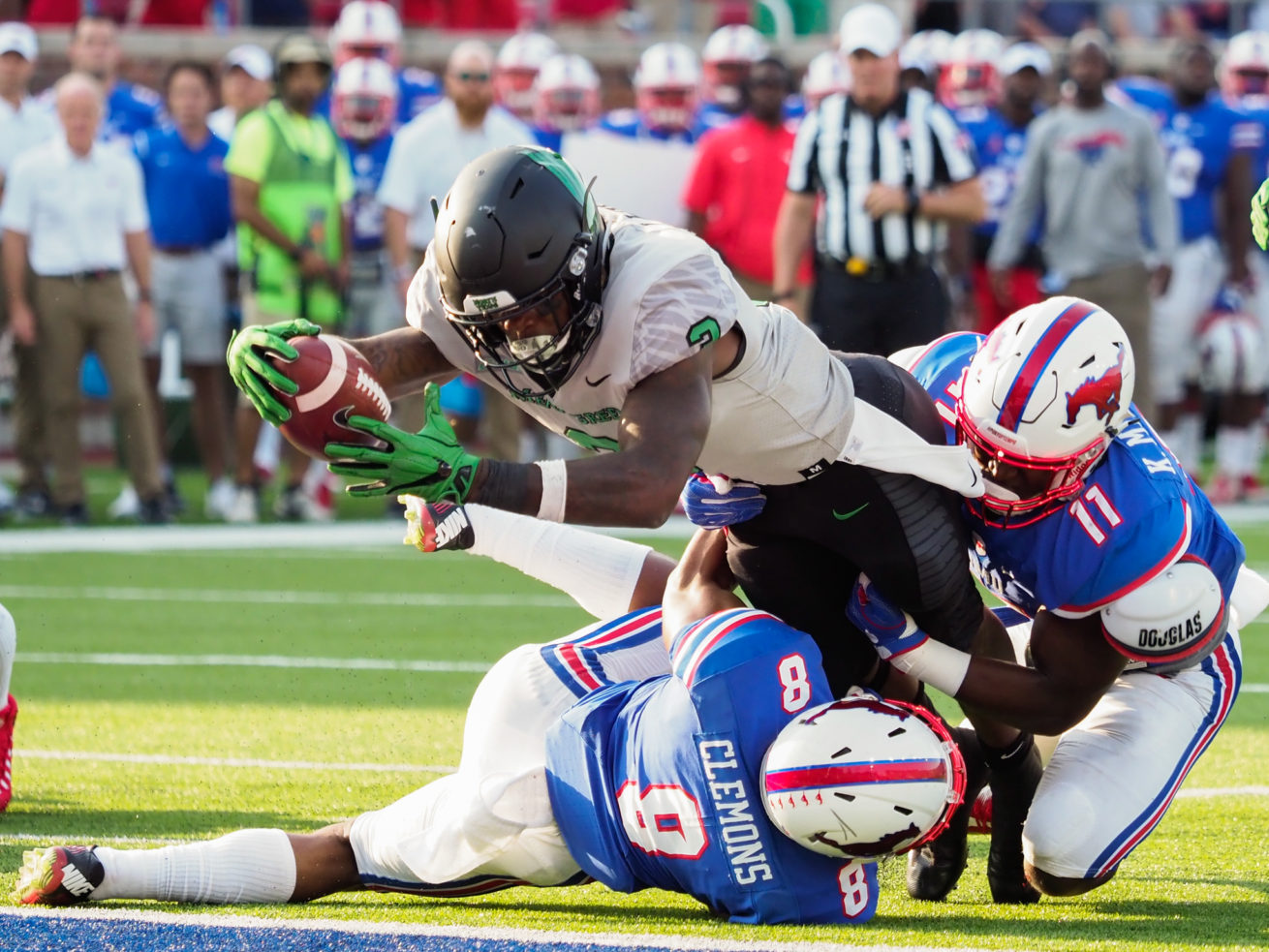 North Texas senior running back Jeffery Wilson (3) lunges to the goal line and scores a touchdown, while being defended by Southern Methodist defensive back Rodney Clemons (8) and Southern Methodist linebacker Kyran Mitchell (11) at Gerald J. Ford Stadium