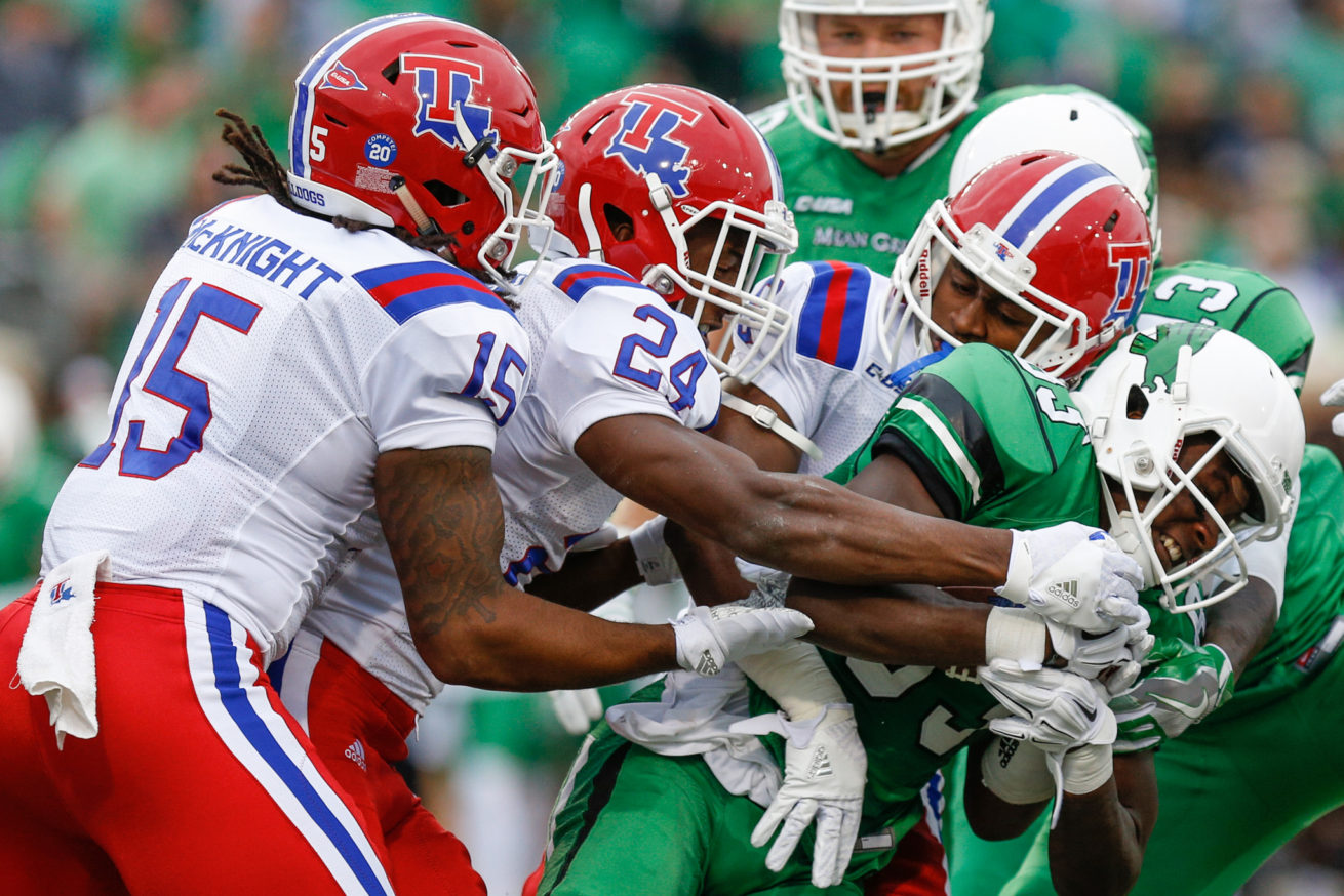 North Texas freshman wide receiver Tyler Wilson (83) returns the ball after a kickoff and the Louisiana Tech defense tackles him at Apogee Stadium