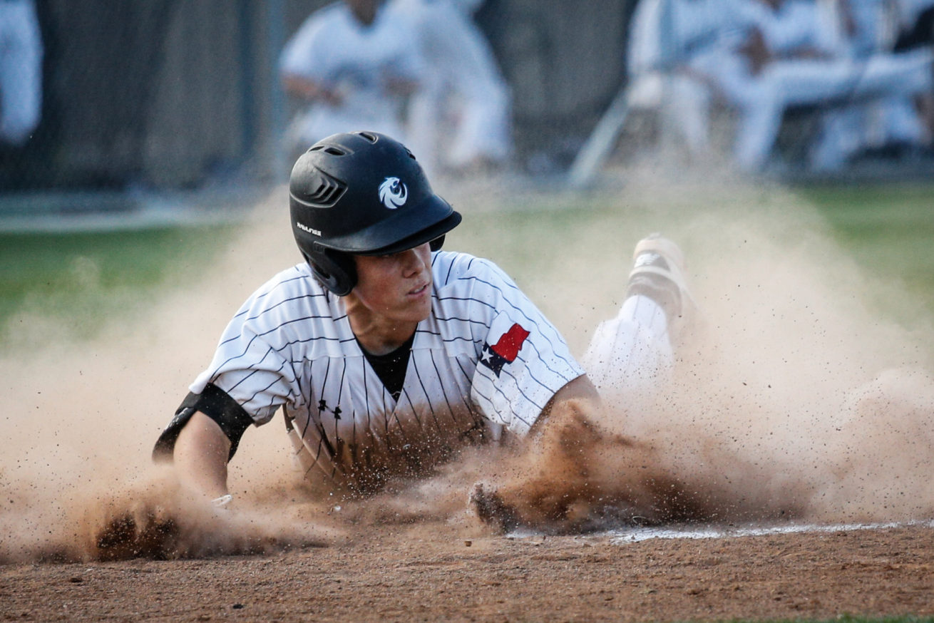 Guyer designated hitter Jordan Beminio (5) slides into home plate and scores against the Boyd defense at the Ballpark at Guyer