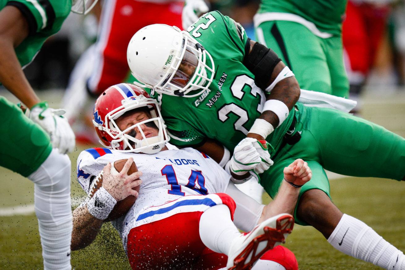 North Texas junior defensive back Kishawn McClain (23) tackles Louisiana Tech senior quarterback Ryan Higgins (14) at Apogee Stadium.  McClain would get thrown out of the game for this hit