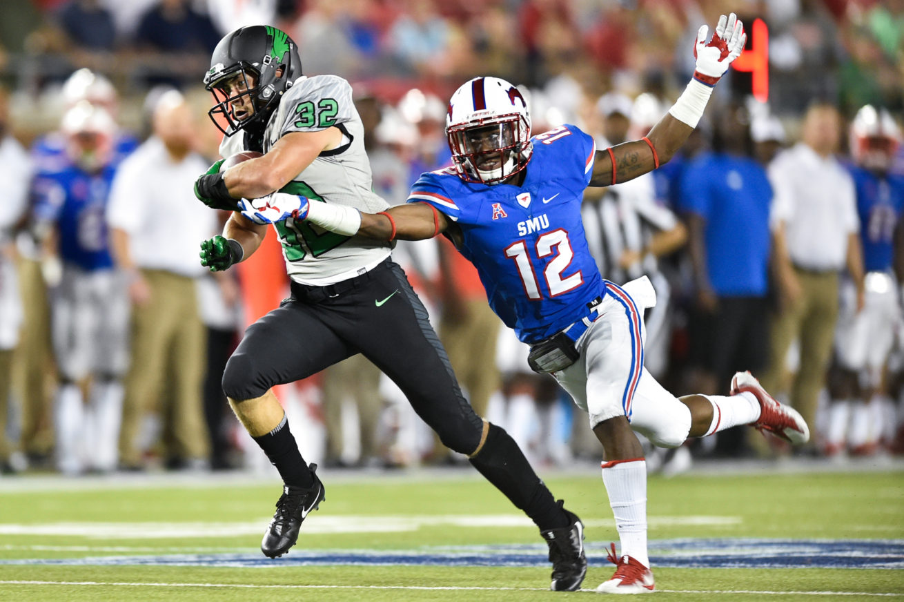 North Texas sophomore wide receiver Michael Lawrence (32)  catches a pass from North Texas sophomore quarterback Mason Fine (6), while being defended by Southern Methodist sophomore safety Kevin Johnson (12) at Gerald J. Ford Stadium.