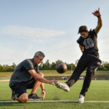 Guyer kicker Cole Schroeder, right, practices kicking field goals with his dad and coach, Cody Schroeder, at Guyer High School.  Cole lost his right eye in a traumatic injury in the spring and has recovered, with an implant and prosthetic, in time to return to the field this season.  Cody coaches the kickers on the football team and is a soccer coach at Guyer High School.